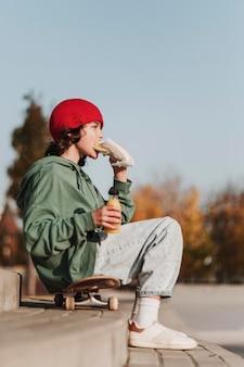 Vue latérale d'un adolescent en train de déjeuner sur une planche à roulettes