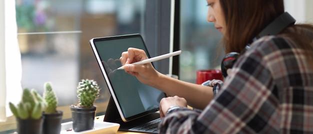 Vue latérale d'une adolescente à l'aide de maquette de tablette numérique sur bar in coffee shop