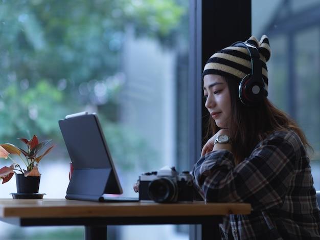 Vue latérale d'une adolescente se détendre avec tablette et casque sur table en bois au café