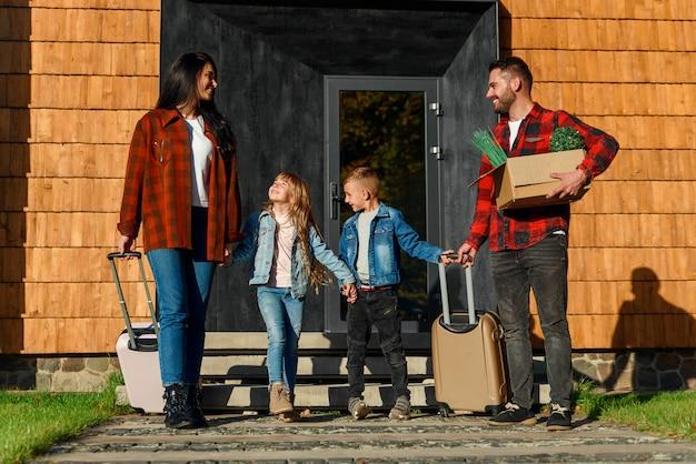 Vue latérale d'adolescents pleins d'entrain et leurs heureux parents de 35 ans qui mettent dans le coffre de la voiture leurs valises et boîte en carton avec des fleurs vertes