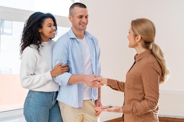 Vue latérale de l'agent immobilier serrant la main avec couple pour nouvelle maison