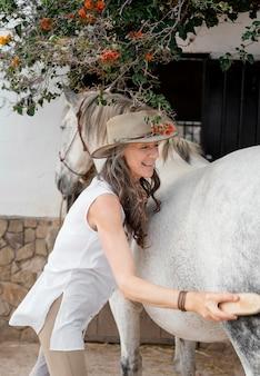 Vue latérale d'une agricultrice brossant son cheval au ranch