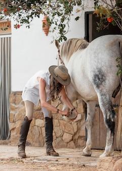 Vue latérale d'une agricultrice nettoyant un fer à cheval au ranch