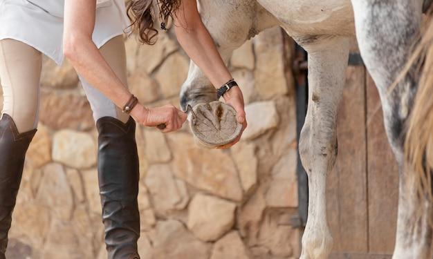 Vue latérale d'une agricultrice nettoyant un fer à cheval