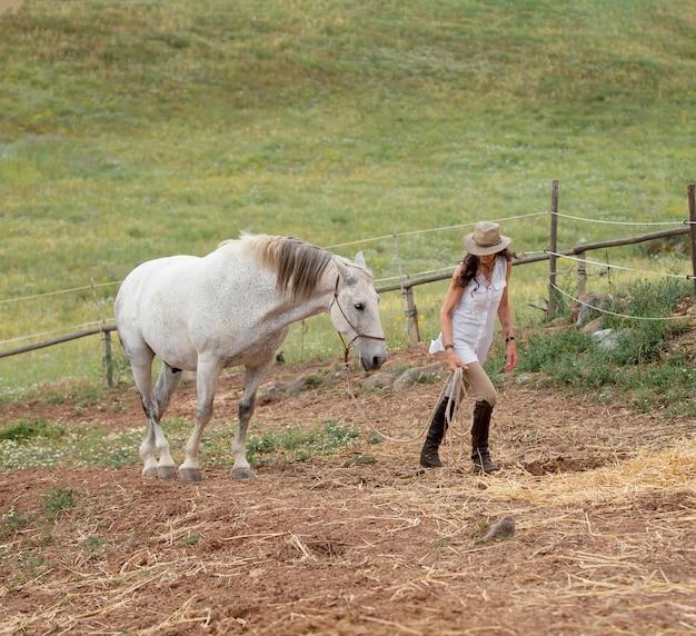 Vue latérale d'une agricultrice avec son cheval à l'extérieur
