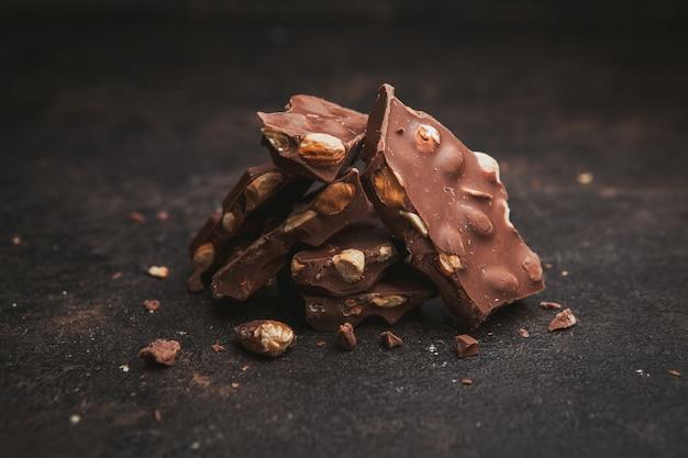 Vue latérale des amandes au chocolat sur une texture marron foncé.