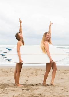 Vue latérale des amies tenant une planche de surf à la plage avec copie espace
