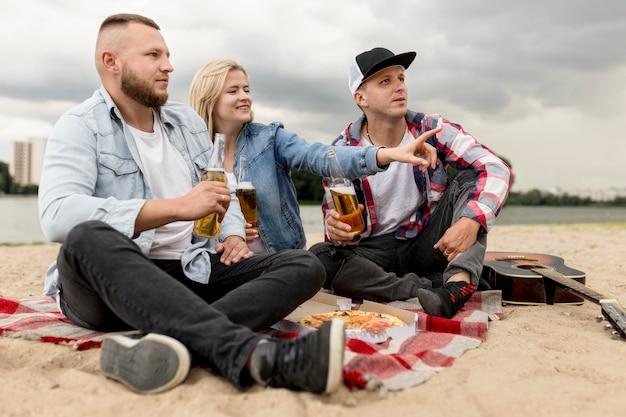Vue latérale des amis assis sur une plage