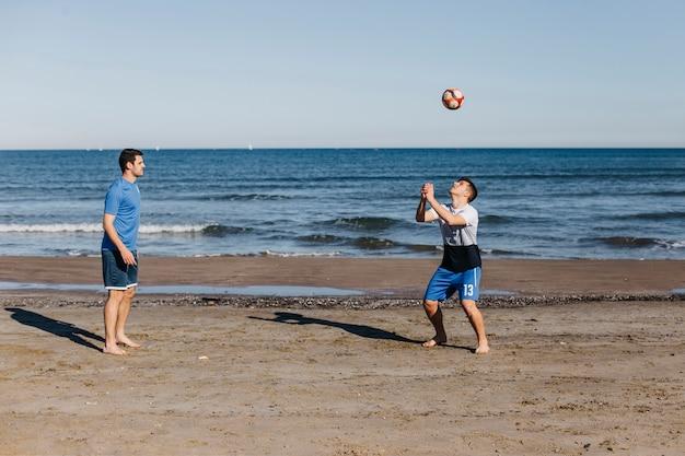 Vue latérale des amis, jouer au football à la plage