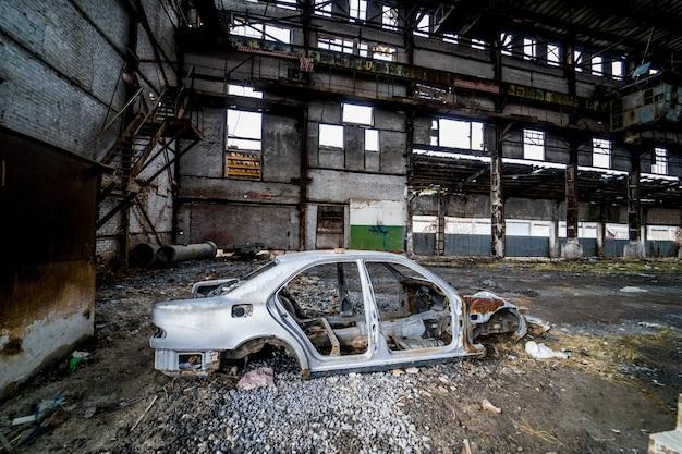 Vue latérale d'un ancien cadre de voiture antique rouillée sur le fond de l'usine en panne.