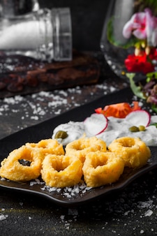Vue latérale des anneaux de calmar dans la pâte avec sauce et salade de légumes frais dans le bac