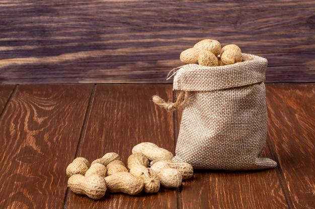 Vue latérale des arachides en coque dans un sac et sur une table en bois