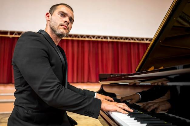 Vue latérale de l'artiste jouant du piano classique