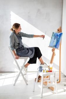 Vue latérale artiste tenant un couteau de peinture