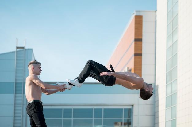 Vue latérale d'artistes hip hop torse nu dansant ensemble à l'extérieur