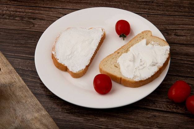 Vue latérale de l'assiette de tranches de pain maculées de fromage cottage et de tomates sur fond de bois