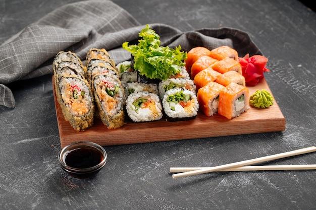 Vue latérale sur un assortiment de rouleaux de sushi sur la planche de bois avec sauce soja