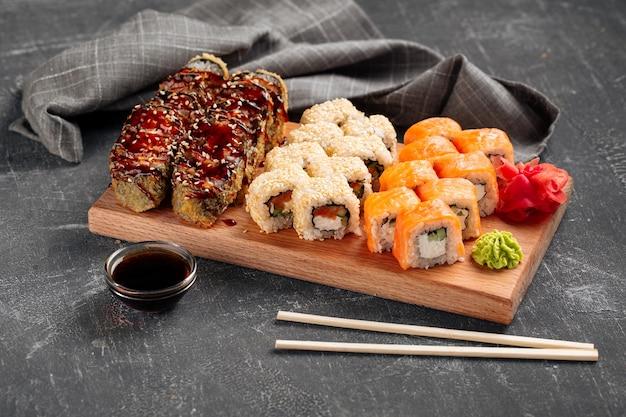Vue latérale sur un assortiment de rouleaux de sushi sur une planche en bois avec wasabi et sauce soja
