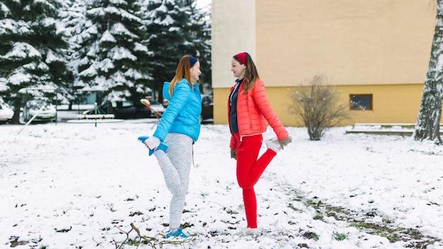 Vue latérale d'athlète féminine qui s'étend de la jambe en hiver