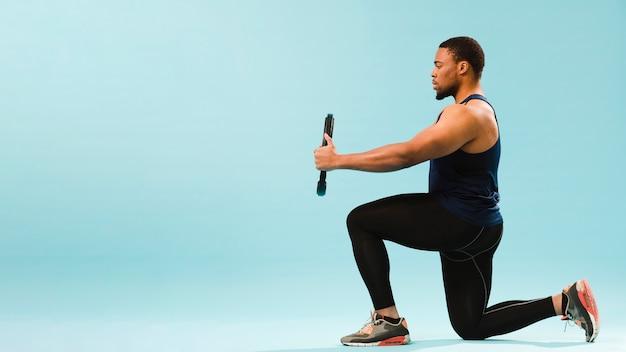 Vue latérale de l'athlète en tenue de gym tenant des poids