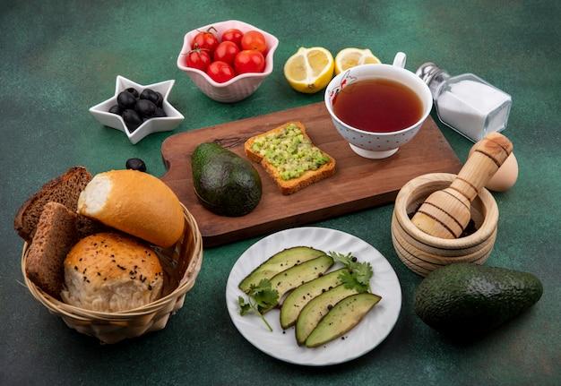 Vue latérale de l'avocat sur une planche de cuisine en bois avec une tasse de thé aux olives noires tomates citrons un seau de pain sur une surface verte