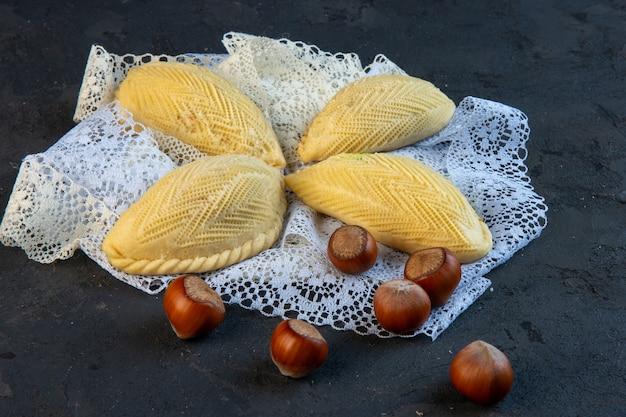 Vue latérale de l'azerbaïdjan dessert national shekerbura aux noisettes sur la dentelle sur fond noir