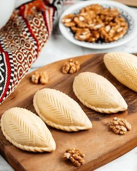 Vue latérale de l'azerbaïdjan dessert national shekerbura sur planche de bois
