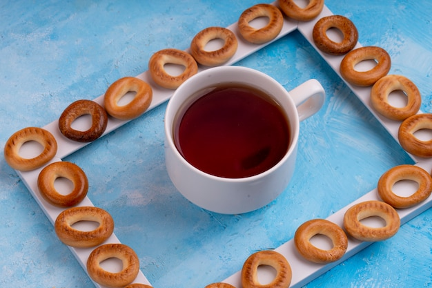 Vue latérale des bagels russes servis avec une tasse de thé sur bleu