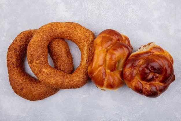 Vue latérale des bagels turcs au sésame croustillants et délicieux avec des petits pains sur fond blanc