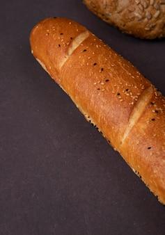 Vue latérale de la baguette française sur fond marron avec espace copie