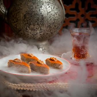 Vue latérale baklava avec verre de thé et fer à repasser théière ancienne en plaque blanche en fumé foncé