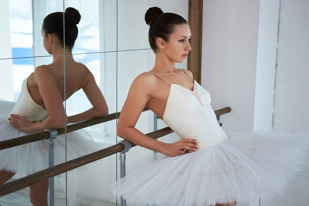 Vue latérale de la ballerine professionnelle s'appuyant sur la barre et regardant ailleurs tout en posant à la caméra. copyspace