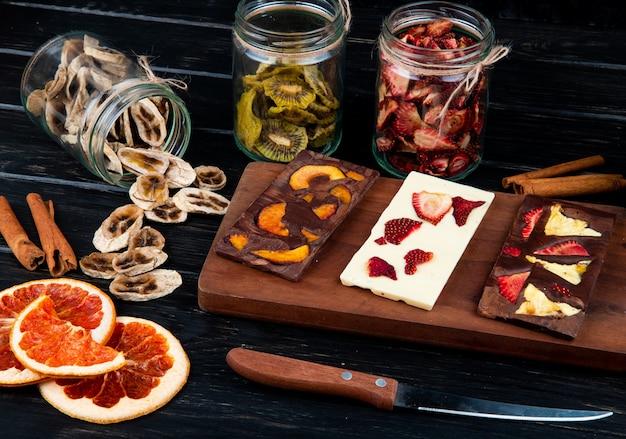 Vue latérale des barres de chocolat noir et blanc sur une planche à découper en bois avec divers fruits en tranches séchées sur fond noir
