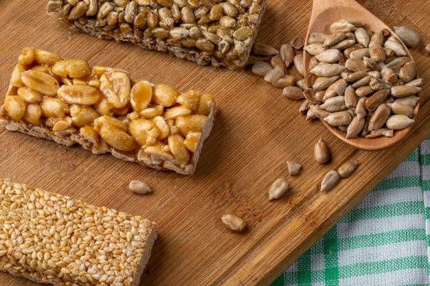 Vue latérale des barres de miel avec des graines de sésame et de tournesol d'arachides sur une planche de bois rustique