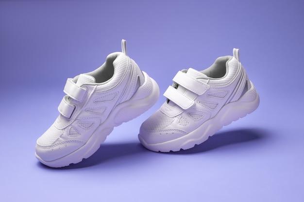 Vue latérale des baskets unisexes blanches avec des attaches velcro, des talons suspendus en l'air isolés sur un fond violet ...