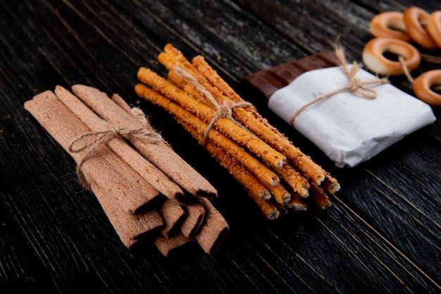 Vue latérale des bâtons de maïs avec des bâtonnets de pain au chocolat et des bagels secs sur un fond en bois noir