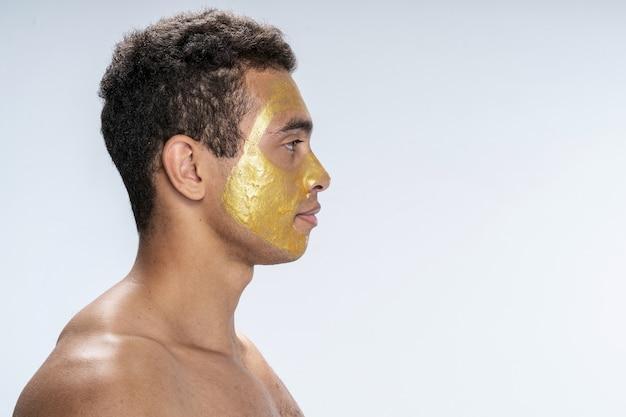 Vue latérale d'un beau mâle portant un masque facial