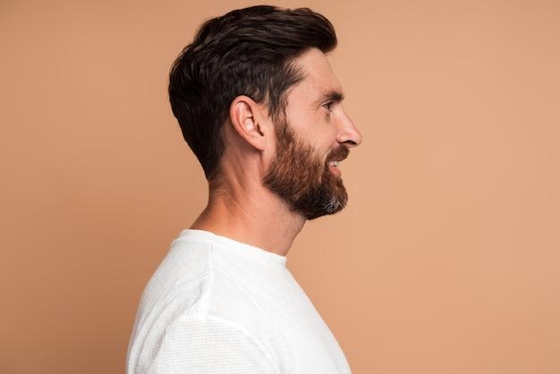 Vue latérale d'un bel homme brune positif avec une barbe en chemise blanche debout avec un sourire de plaisir et en détournant les yeux avec une expression joyeuse. studio intérieur tourné isolé sur fond beige