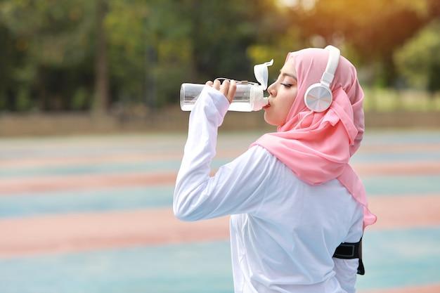 Vue latérale belle athlète fitness femme musulmane eau potable après le travail sur l'exercice. jeune jolie fille debout dans des vêtements de sport se reposer après une séance d'entraînement en plein air. concept sain et sportif