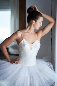 Vue latérale de la belle ballerine debout et regardant à travers la fenêtre. copyspace