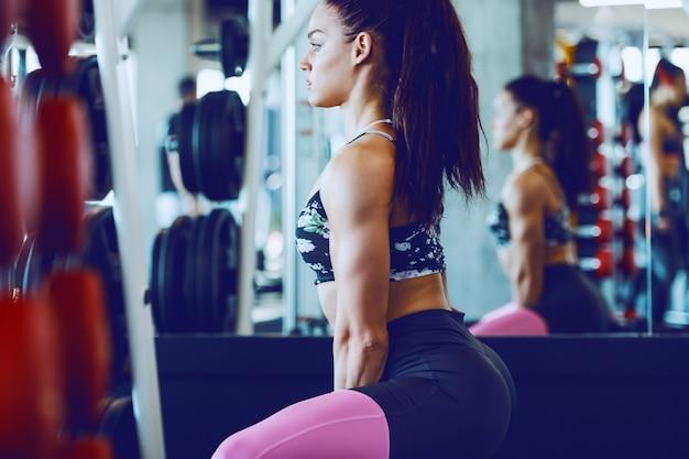 Vue latérale de la belle caucasienne brune musclée sportswear soulevant la cloche de la bouilloire dans la salle de gym. concept de musculation.