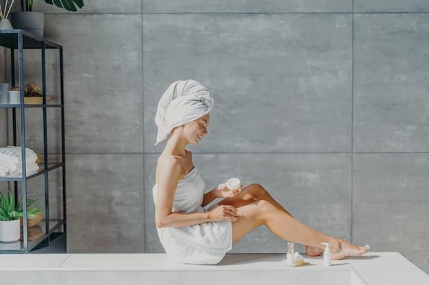 Vue latérale belle femme appliquant la lotion