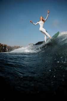 Vue latérale belle femme blonde en maillot de bain blanc debout sur le wakeboard levant les mains