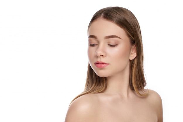 Vue latérale d'une belle femme avec du maquillage nude, regardant vers le bas sur un fond isolé blanc.