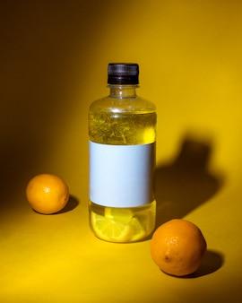 Vue latérale d'une boisson détox au citron dans une bouteille sur jaune foncé