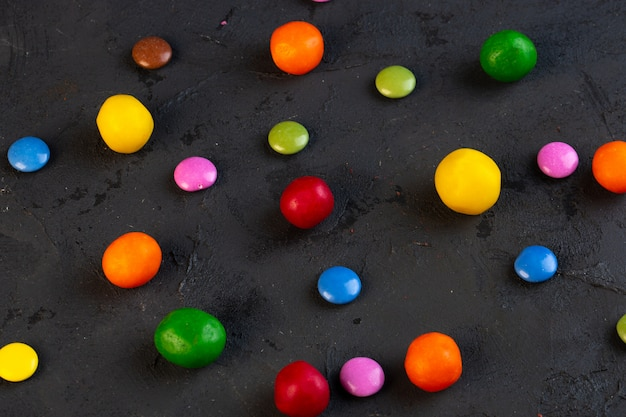 Vue latérale de bonbons colorés dispersés sur fond noir