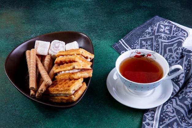 Vue latérale bonbons gaufres petits pains sucrés et marmelade avec une tasse de thé sur vert