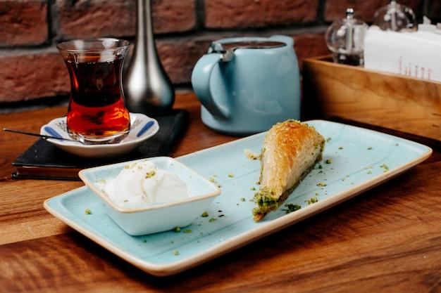 Vue latérale de bonbons turcs baklava de forme triangulaire avec pistache servi avec de la crème glacée sur le plateau