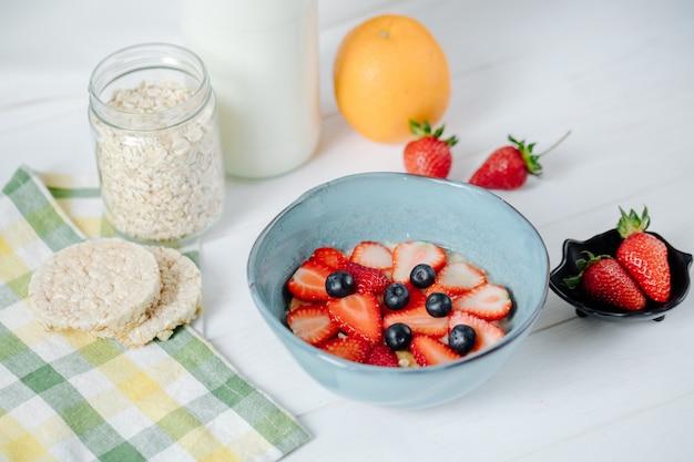 Vue latérale de la bouillie d'avoine avec des fraises et des bleuets en tranches dans un bol en céramique sur la table