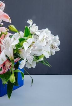 Vue latérale d'un bouquet de fleurs d'alstroemeria de couleur rose et blanc dans une boîte bleue sur fond gris